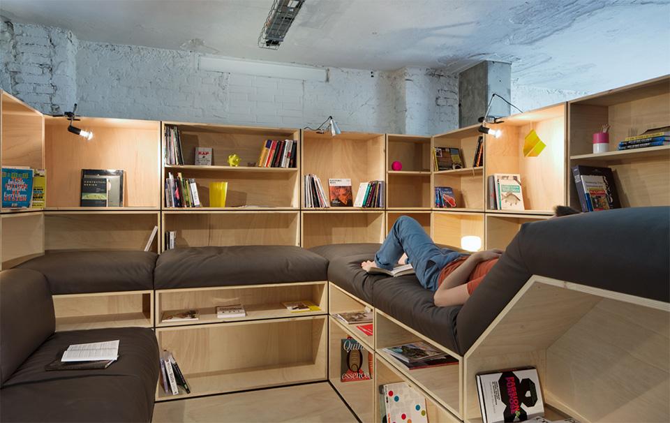 O escritório conta com uma pequena biblioteca. Na prateleira, alguns livros de design e revistas alemãs