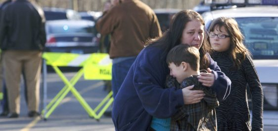 A young boy is comforted outside Sandy Hook Elementary School af