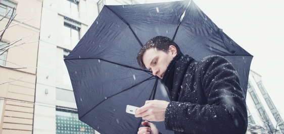 videoblocks-young-man-using-a-smartphone-typing-sms-scrolling-pictures-phone-standing-with-umbrella-under-snowfall-city-alley-on-the-background-slow-motion-low-angle-shooting_bfv6iztcg_thumbnail-full01