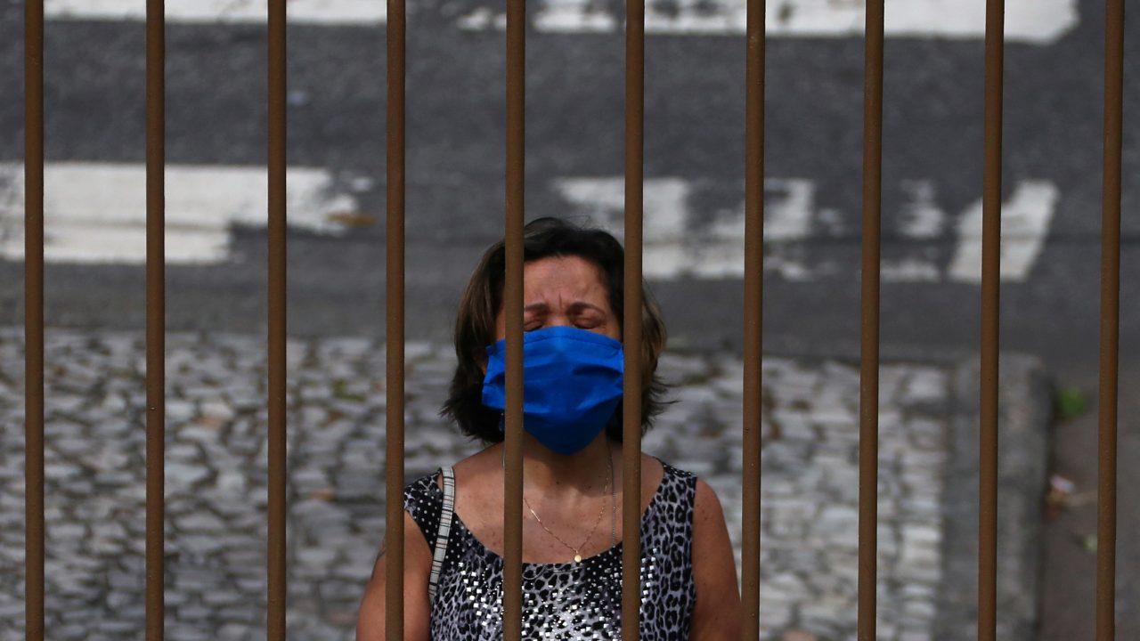 A woman wearing a protective face mask prays outside a church as priest Jorge Luiz de Oliveira delivers the Angelus prayer from the balcony of the Santuario Basilica de Sao Sebastiao, following the coronavirus disease (COVID-19) outbreak, in Rio de Janeiro