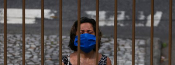 A woman wearing a protective face mask prays outside a church as priest Jorge Luiz de Oliveira delivers the Angelus prayer from the balcony of the Santuario Basilica de Sao Sebastiao, following the coronavirus disease (COVID-19) outbreak, in Rio de Janeiro