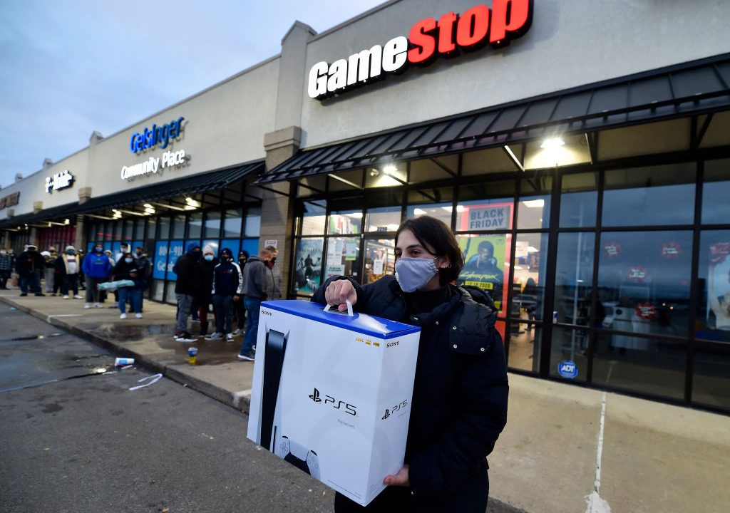 A man wearing a face masks leaves Game Stop with the new